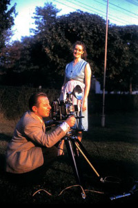 1950s-vintage-color-photo-man-with-bellows-camera-and-flash-outdoors-with-woman-in-apron